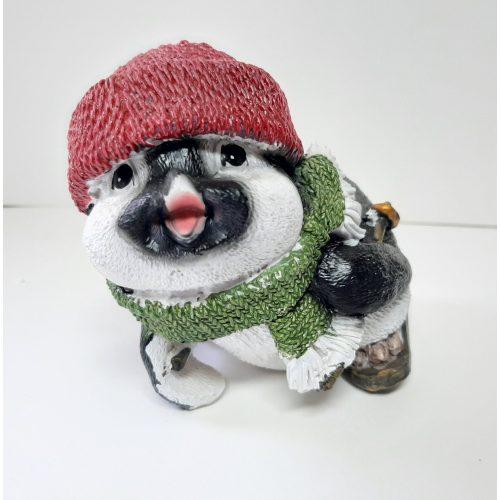 Beeldje pinguin op skis met rode muts en groene sjaal voorover