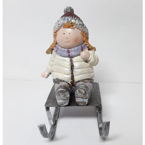 Decoratief beeldje meisje op slee in winter kleding